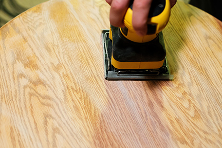 Sanding the table top with a palm sander