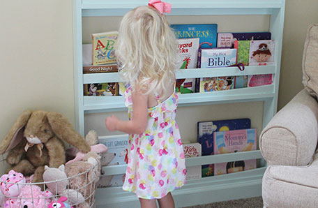 Young girl in polka dot dress taking a book from the bookshelf
