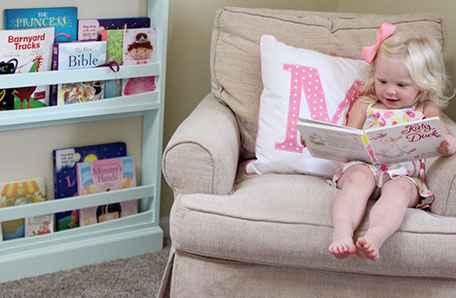 Young girl sitting in a chair, reading a book