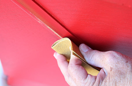 Use fine-grit sandpaper to rub off paint for a distressed look