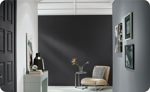 Gray room with dark wall, chair, frames on the wall.