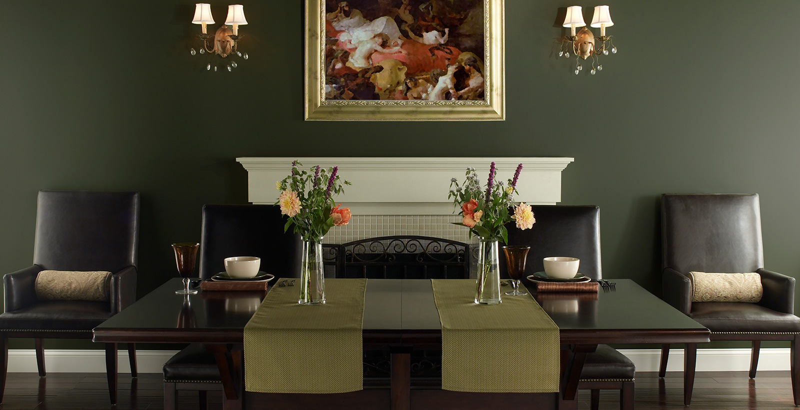 Stately traditional dining room with rich moss green on walls and white paint on fireplace mantle and trim. Leather dining chairs surround dark wood table.