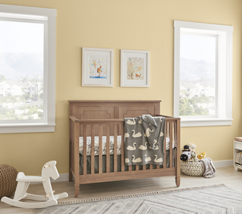 A decorated baby nursery with light yellow walls, a wooden crib, and a white rocking horse.