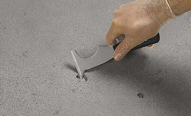 Image of a hole in concrete with a tool showing how to fix it.