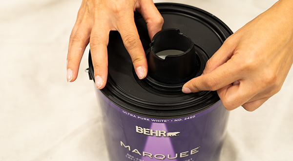 Close up of person placing Simple Pour Lid on can.