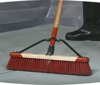 Person using a large broom to sweep the floor