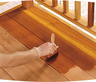 Person staining wood deck with paint brush