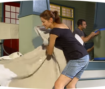 Man and woman cleaning up after painting walls