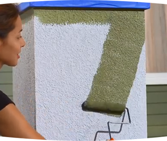 Person rolling on paint to the outside of a house