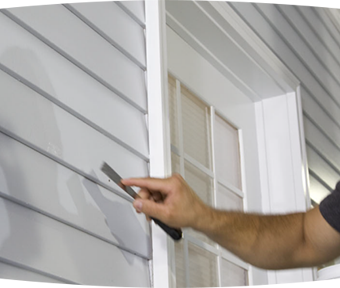 Person with a joint knife repairing siding of a house