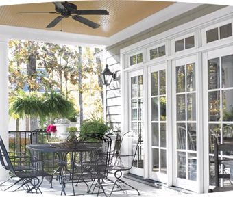 Outdoor patio area with a table, chairs, and a ceiling fan