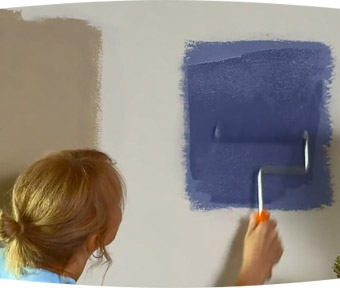 Person applying paint to a wall with a paint roller