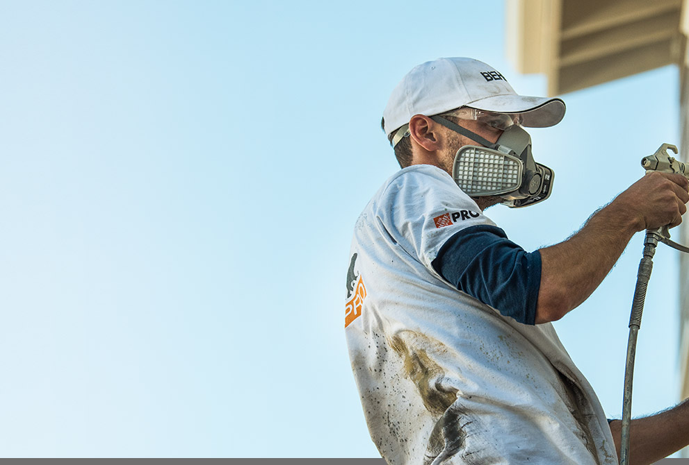 Image of a Pro Contractor wearing a hat and shirt with Behr logo spray painting an exterior wall of a house on a ladder.