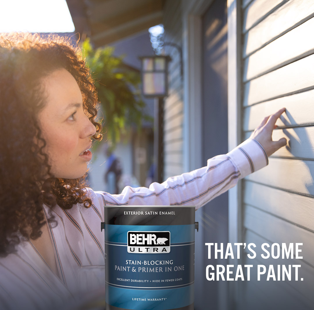 Mobile-sized photo of woman examining exterior house siding, can of Behr Ultra Interior Satin Enamel in foreground with text overlay that's some great paint.