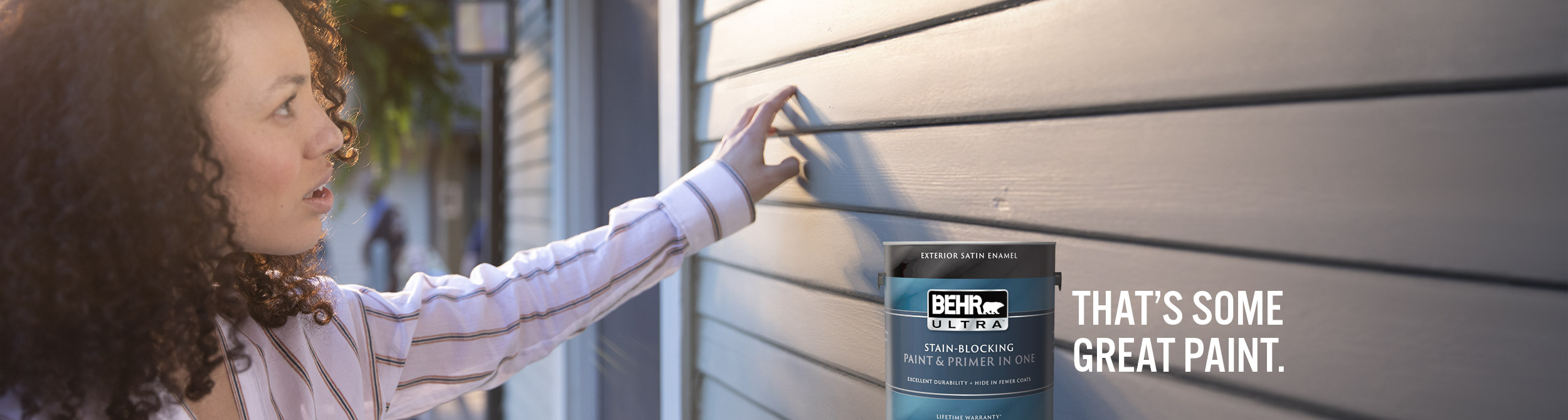 Photo of woman examining exterior house siding, can of Behr Ultra Interior Satin Enamel in foreground with text overlay that's some great paint.