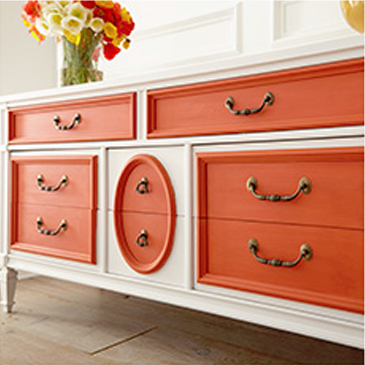 Orange and white dresser with flowers on the table