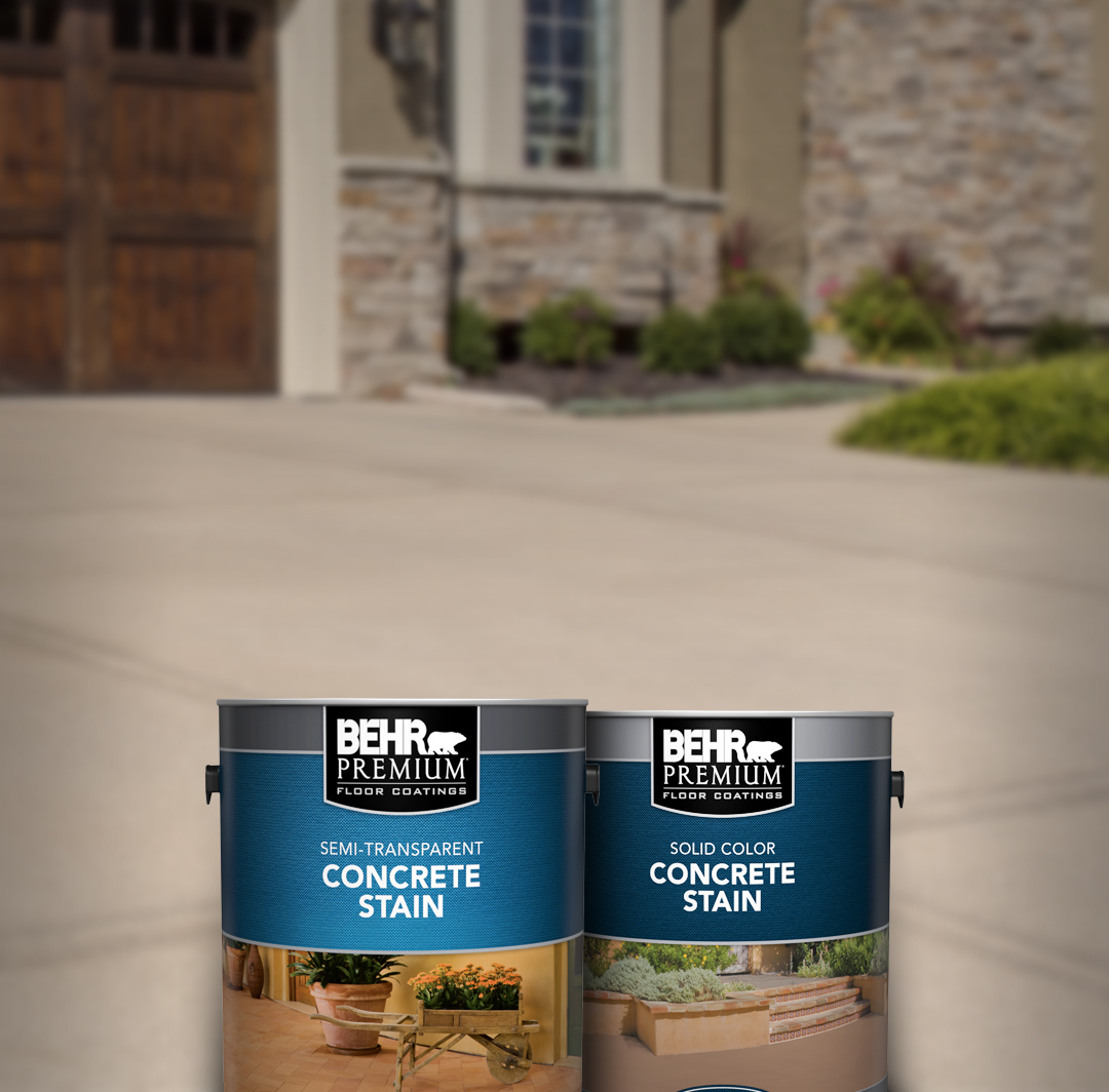 Two cans of Behr paint with brick house and driveway in the background