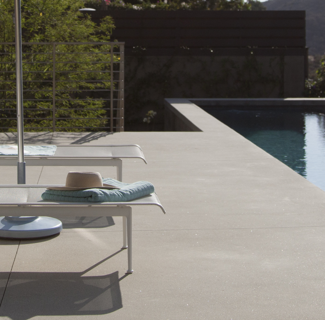 Two pools chairs next to a pool