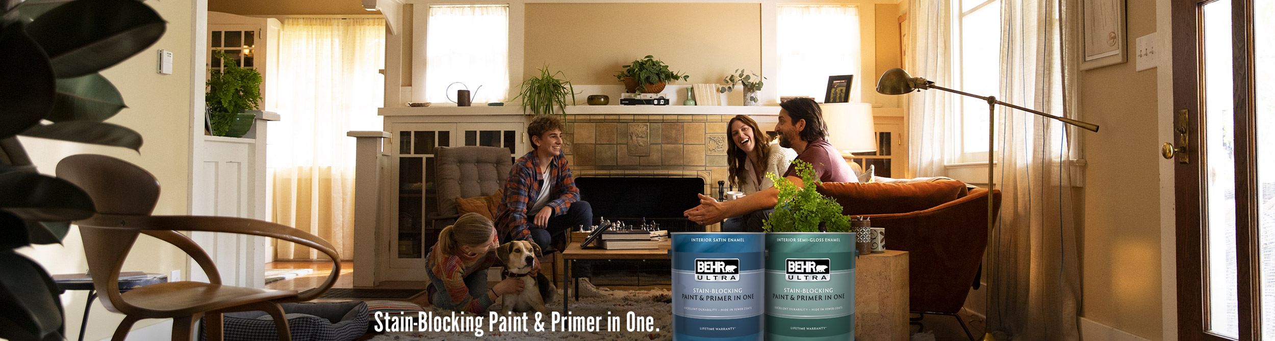 Family sitting in their family room,  Gallon cans of Ultra Interior Satin Enamel and Semi-Gloss paint in foreground.