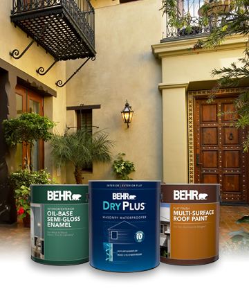 Three cans of Behr Paint with tan house in the background
